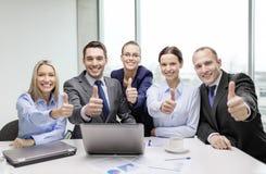 Equipe do negócio que mostra os polegares acima no escritório fotos de stock royalty free