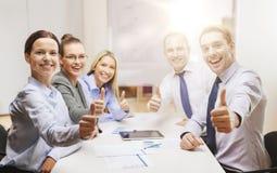 Equipe do negócio que mostra os polegares acima no escritório fotografia de stock