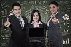 Equipe do negócio que mostra a tela vazia no portátil imagem de stock royalty free