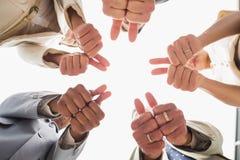 Equipe do negócio que olha para baixo na câmera que mostra os polegares acima Imagem de Stock