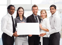 Equipe do negócio que prende um cartão em branco foto de stock