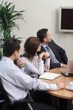 Equipe do negócio que presta atenção à tevê Foto de Stock