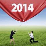 Equipe do negócio que puxa um ano novo de 2014 Fotografia de Stock Royalty Free