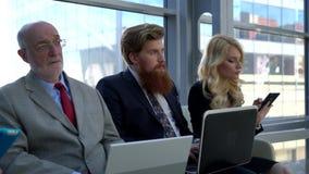 Equipe do negócio que senta-se em seguido video estoque
