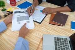 Equipe do negócio que senta-se em torno da tabela e que trabalha com relatório de papel da carta sócios bem sucedidos que discute imagem de stock