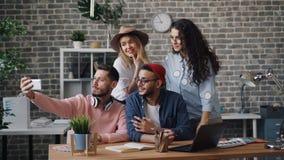 Equipe do negócio que toma o selfie no escritório usando a câmera do smartphone que levanta o sorriso filme