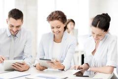 Equipe do negócio que trabalha com os PCes da tabuleta no escritório Imagens de Stock