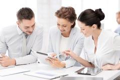 Equipe do negócio que trabalha com os PCes da tabuleta no escritório Imagem de Stock
