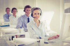 Equipe do negócio que trabalha em computadores e em auriculares vestindo Imagens de Stock
