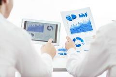 A equipe do negócio que usa a tabuleta digital analisa o relatório de mercado fotografia de stock