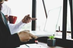 Equipe do neg?cio que analisa cartas e gr?ficos da renda com laptop moderno imagens de stock royalty free