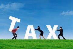 A equipe do negócio constrói uma palavra do imposto Imagens de Stock