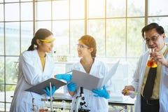 Equipe do projeto novo da pesquisa asiática nova do químico da mulher com o professor do homem no laboratório fotografia de stock royalty free