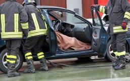 A equipe do sapador-bombeiro extrai a pessoa do interior do carro após a Imagens de Stock Royalty Free