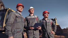 Equipe do trabalhador masculino profissional do construtor no canteiro de obras no tiro m?dio do por do sol video estoque