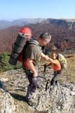 Equipe a doação da mão amiga ao amigo ao penhasco da rocha da montanha da escalada Fotografia de Stock