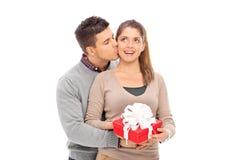 Equipe a doação de um presente a sua amiga e o beijo dela Fotografia de Stock