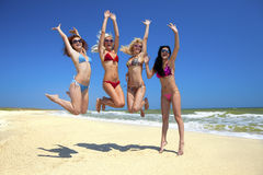 Equipe dos amigos que saltam na praia fotografia de stock