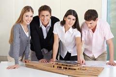 Equipe dos arquitetos em torno do modelo 3D Fotografia de Stock