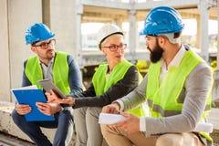Equipe dos arquitetos novos bem sucedidos que discutem detalhes do projeto durante uma reuni imagem de stock