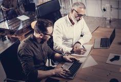Equipe dos colegas de trabalho que fazem a grande discussão do trabalho no escritório moderno Homem farpado adulto que escreve id Fotografia de Stock