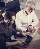 Equipe dos colegas de trabalho que fazem a grande discussão do trabalho no escritório moderno Homem farpado adulto que escreve id Fotografia de Stock Royalty Free