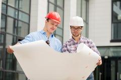 A equipe dos construtores está trabalhando concordando o plano e o esquema fotografia de stock royalty free