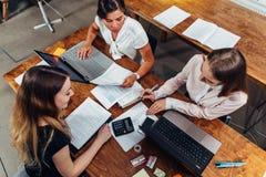 Equipe dos contadores fêmeas que preparam o relatório financeiro anual que trabalha com papéis usando os portáteis que sentam-se  imagens de stock