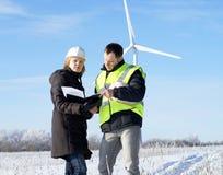 Equipe dos coordenadores com turbinas eólicas Foto de Stock Royalty Free