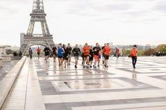 Equipe dos corredores que correm no fundo da torre Eiffel no quadrado de Trocadero, Paris imagem de stock