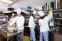Equipe dos cozinheiros chefe que preparam o alimento na cozinha Foto de Stock Royalty Free