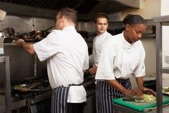 Equipe dos cozinheiros chefe que preparam o alimento na cozinha do restaurante Fotografia de Stock Royalty Free