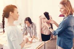 Equipe dos desenhistas bem sucedidos que discutem a coleção nova da roupa fotografia de stock