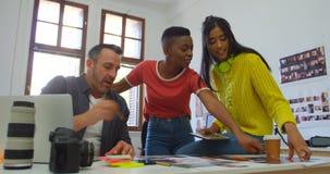 Equipe dos designer gráficos que discutem sobre as fotos 4k vídeos de arquivo