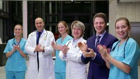 Equipe dos doutores e do homem de negócios que aplaudem durante a reunião
