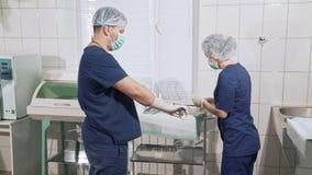 A equipe dos doutores está sendo preparada para a operação O assistente da enfermeira ajuda o cirurgião posto sobre as luvas bran vídeos de arquivo