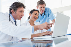 Equipe dos doutores felizes que trabalham no laptop Foto de Stock Royalty Free