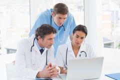 Equipe dos doutores que trabalham no laptop Fotografia de Stock