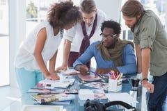 Equipe dos editores de fotos que têm a sessão da sessão de reflexão Imagens de Stock