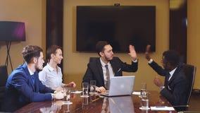 Equipe dos empresários novos que encontram-se no escritório que discute o plano de negócios video estoque
