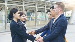 a equipe dos executivos do homem e mulher espertos fala e agita a mão Imagem de Stock Royalty Free