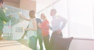 Equipe dos executivos empresariais que discutem sobre a placa de vidro vídeos de arquivo