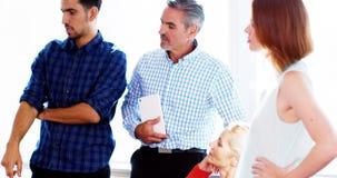 Equipe dos executivos empresariais que têm uma discussão na reunião video estoque
