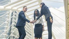 A equipe dos executivos fala e junta-se à mão no bom sentimento na OU Imagem de Stock