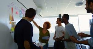 Equipe dos executivos que discutem sobre notas pegajosas no whiteboard video estoque