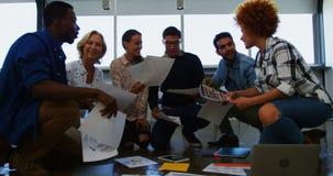 Equipe dos executivos que discutem sobre o original na reunião video estoque