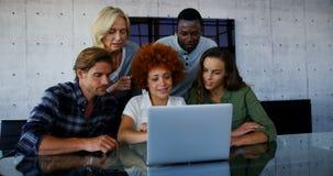 Equipe dos executivos que discutem sobre o portátil video estoque
