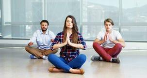 Equipe dos executivos que praticam a ioga