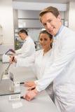 Equipe dos farmacêuticos que usam a imprensa para fazer comprimidos Fotografia de Stock