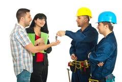 A equipe dos homens do construtor dá chaves da casa a um par Fotos de Stock